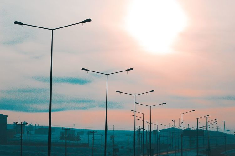 Low angle view of street lights against sky during sunset