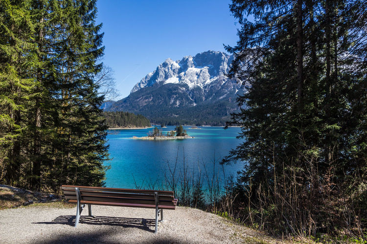 bench at Eibsee below Zugspitze Idyllic Panoramic Panorama Turquoise Colored Island Snowcapped Mountain Green Green Color Clear Water Travel Destinations Clear Sky Blue Blue Sky Springtime Spring Fir Tree Bavarian Alps Bavaria Alps Zugspitze Eibsee View Sunlight Relaxing Meditation Mountain Beauty In Nature Scenics - Nature Water Tranquil Scene Plant Sky Nature Tranquility Tree Non-urban Scene Seat Lake Day No People Mountain Range Bench Outdoors