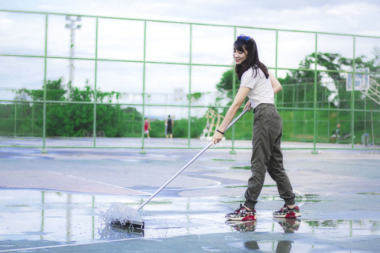 Young woman cleaning water from basketball court