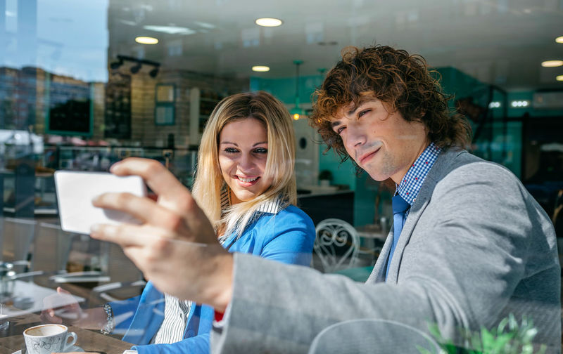 Smiling young woman using smart phone