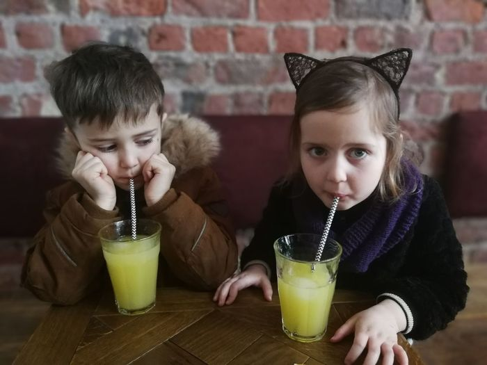 Siblings drinking juice in restaurant