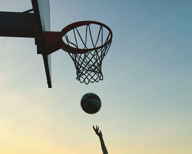 Cropped Hands Playing Basketball Against Clear Sky During Sunset