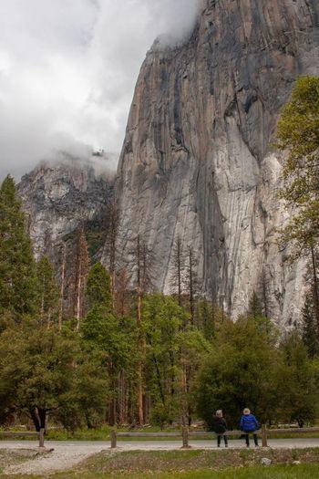 Rear view of people walking on rock against sky