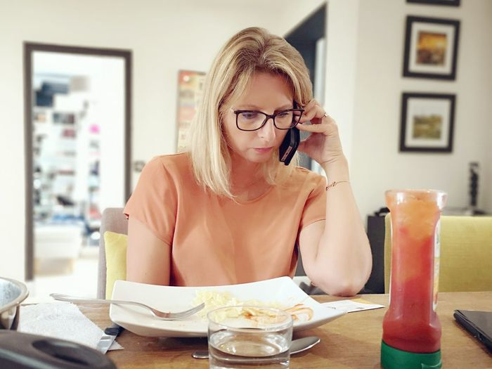 Woman Talking On Smart Phone While Sitting On Table