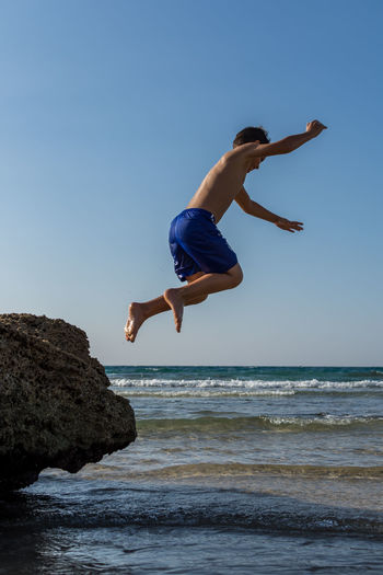 Full length side view of shirtless boy jumping from rock into sea