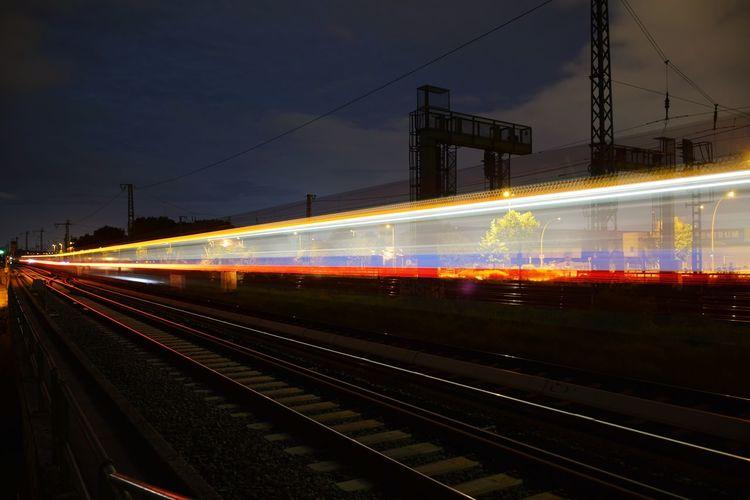 Light trails on railroad station platform at night