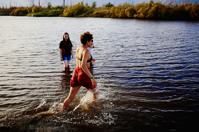 Ankle Deep In Water Beauty In Nature Bonding Day Enjoyment Full Length Fun Happiness Lake Leisure Activity Lifestyles Nature Outdoors Real People Rippled Smiling Togetherness Tree Two People Vacations Water Waterfront Young Adult Young Women