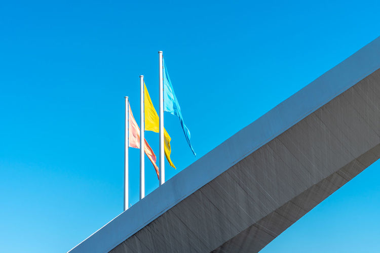 Blue Flag Summer In The City Architecture Blue Blue Sky Built Structure Clear Sky Copy Space Day Environment Flag Flags In The Wind  Independence Low Angle View National Icon Nature No People Outdoors Patriotism Pole Pride Red Flag Sky Striped Three Flags Waving Wind Yellow Flag 17.62°