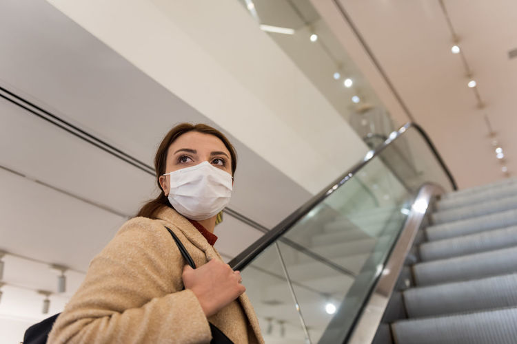 Low angle view of woman wearing mask sanding on escalator at shopping mall