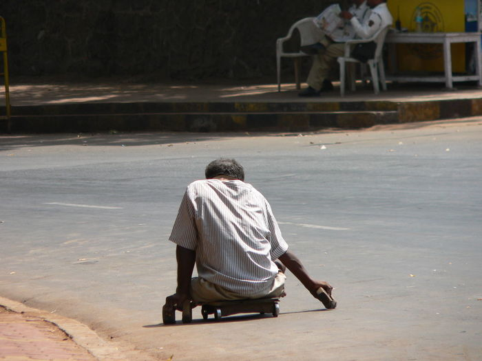Disabled beggar on cart over road in city