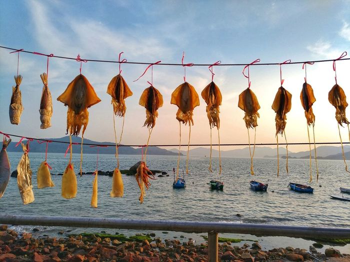 Clothes drying on rope at beach against sky