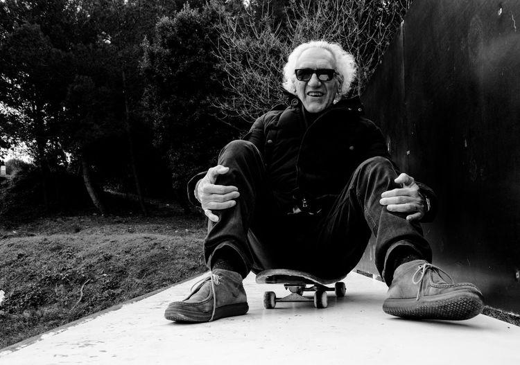 Portrait Of Man Sitting On Skateboard Against Plants