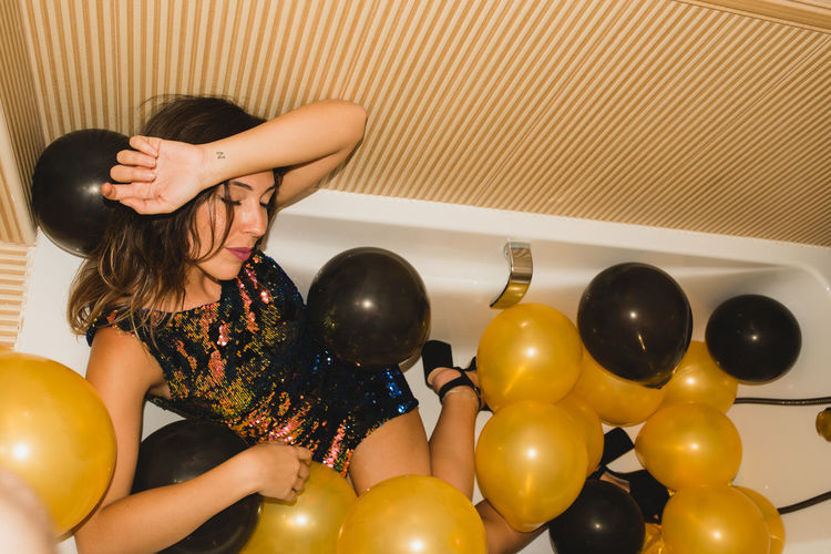 Midsection of woman holding balloons at home