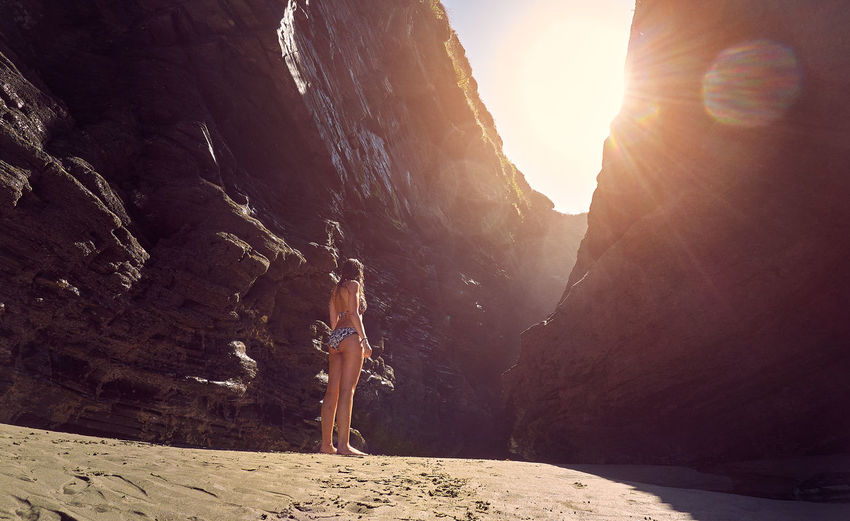 Rear view of woman wearing bikini standing amist rock formation against sky