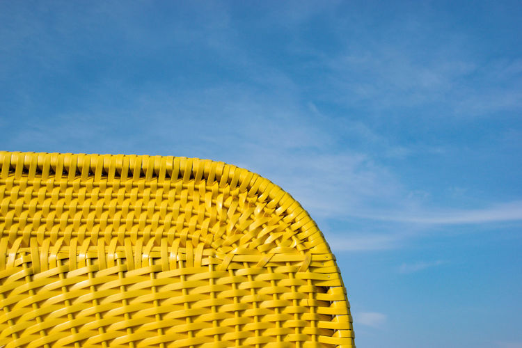 Low angle view of yellow metallic structure on beach against sky
