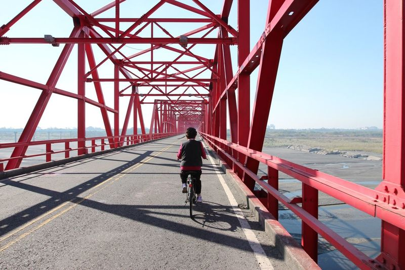 Rear View Of Man Riding A Bike On Bridge Over Sea Against Clear Sky
