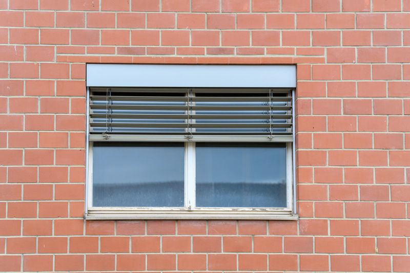 Close-up of window on brick wall of building