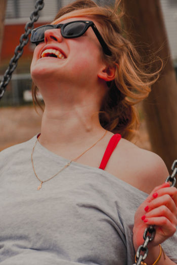Close-up of cheerful woman enjoying swing at playground