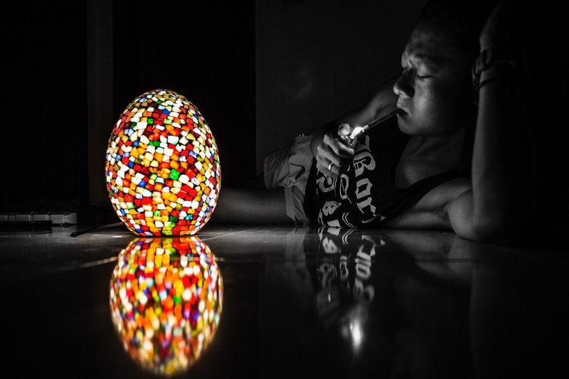 Midsection of illuminated lantern on table