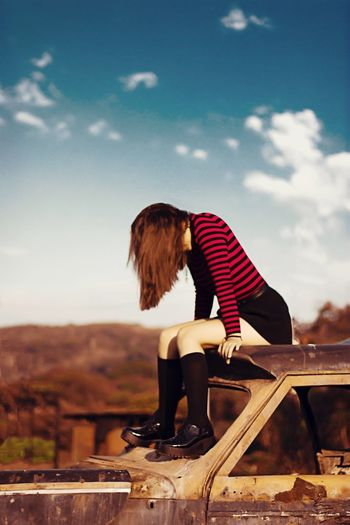 Full length of woman sitting on abandoned car against sky