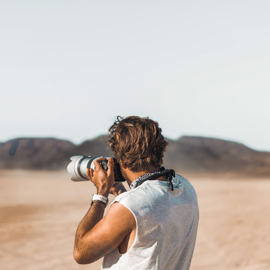 Rear view of man standing on land holdings camera taking photos