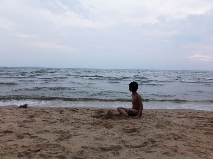 Shirtless boy looking at sea while playing with sand on shore against sky