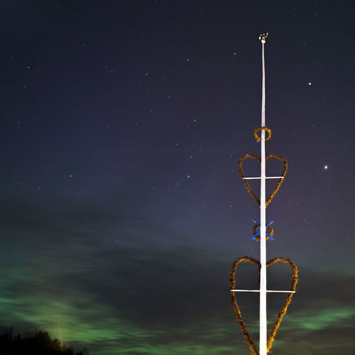 Low angle view of heart shape on pole against dramatic sky at night