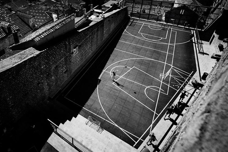 High angle view of boy playing basket ball at court