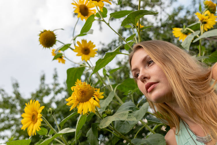 Low angle view of woman looking away against plants