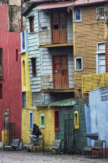 Full length of man sitting on street against buildings in city