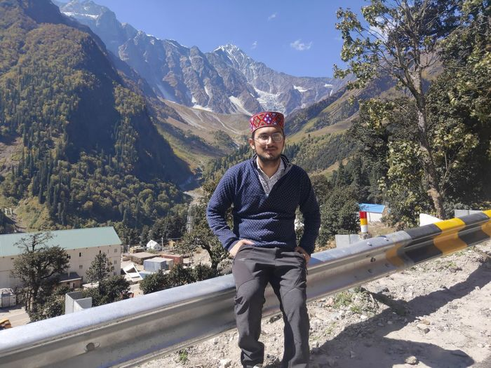 Full length portrait of young man against mountains