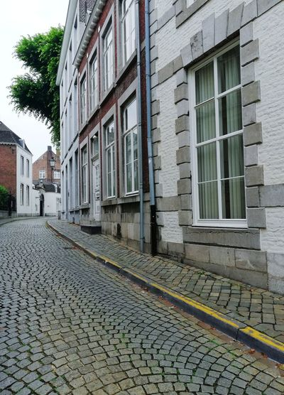 MAASTRICHT, NETHERLANDS - JUNE 10, 2018 : Street of old city center of Maastricht. Europe Trip Netherlands Dutch Traditional Urban Style Travel Destinations Typical Cultural Streetphotography Street Walking Walking Around Travel Destinations Tourist Destination Visiting Nobody Street Old City Building Town City Street City Center Building Facades Empty Road Empty Places Wall Backgrounds Outdoors Railroad Track
