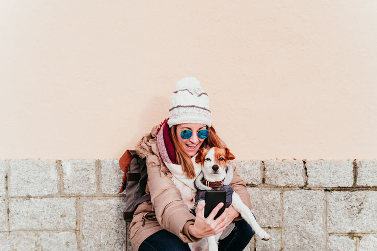 Cheerful woman taking selfie with dog against wall