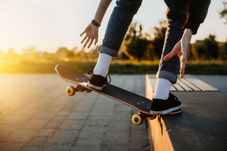 Low section of man skateboarding on street