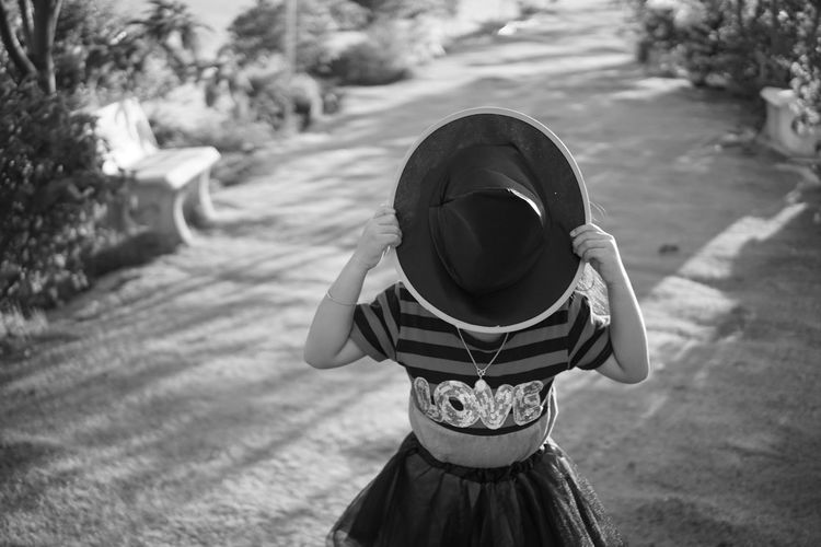 Girl holding hat while standing in park