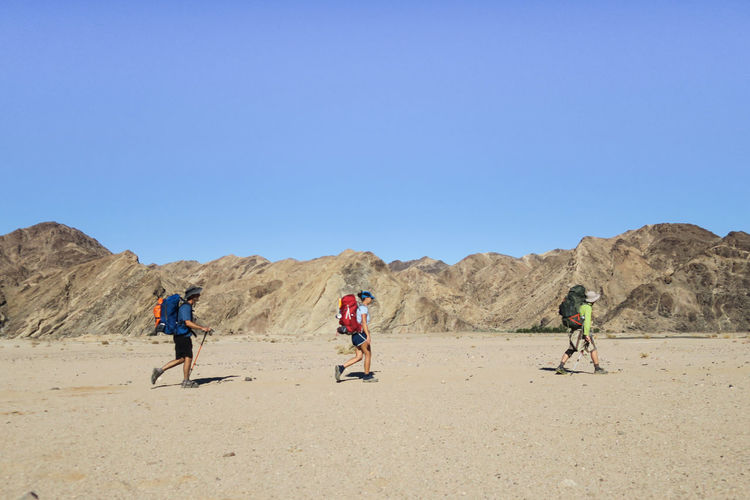 Group of hikers walking through desert in straight line Adventure Arid Climate Backpack Bag Clear Sky Desert Explore Group Of People Hikers Hiking Landscape_Collection Let's Go. Together. Mountain Mountain Range Namibia Nature Outdoor Photography Outdoors Team Travel Wilderness