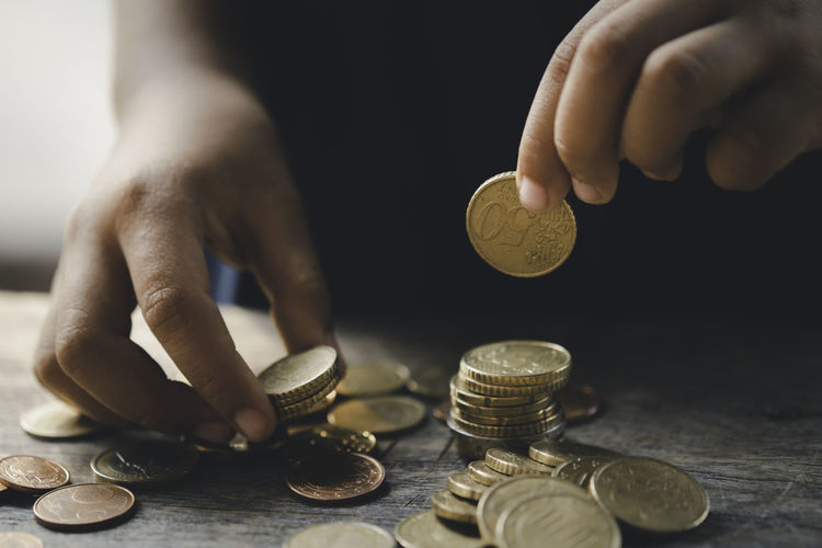 Close-up of hand holding coins over table