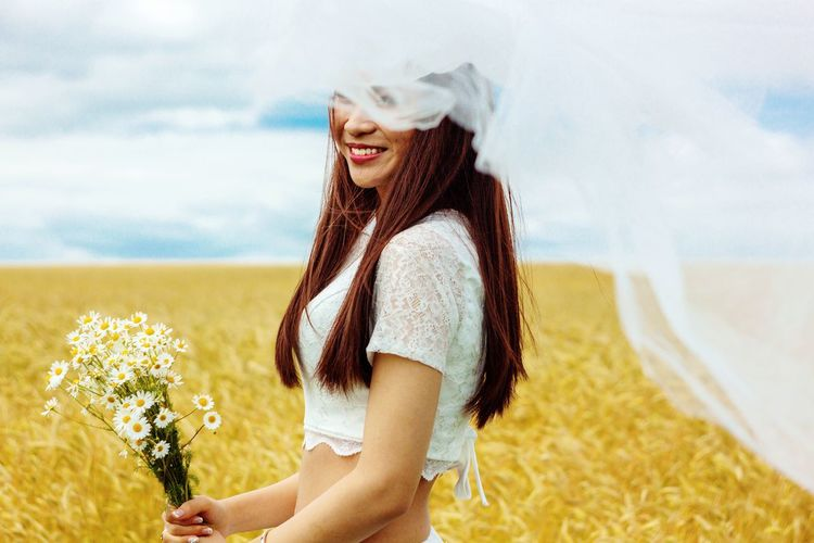 Smiling bride in veil with flowers standing on agricultural field