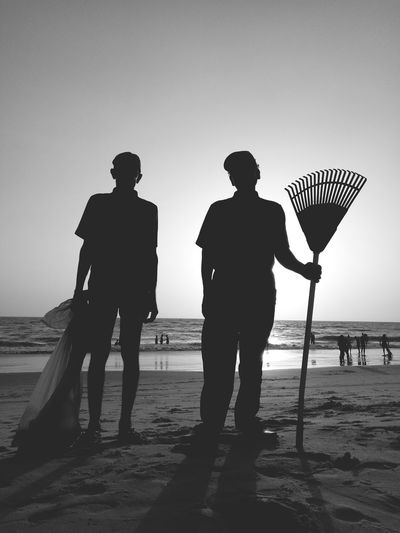 Silhouette workers standing at beach against clear sky