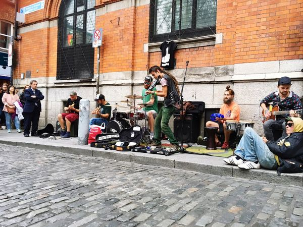 Investing In Quality Of Life Brick Wall Building Exterior Musical Instrument Architecture Music Arts Culture And Entertainment Real People Guitar City Built Structure Sitting Outdoors Plucking An Instrument Day Playing Men Lifestyles Musician Electric Guitar Adult