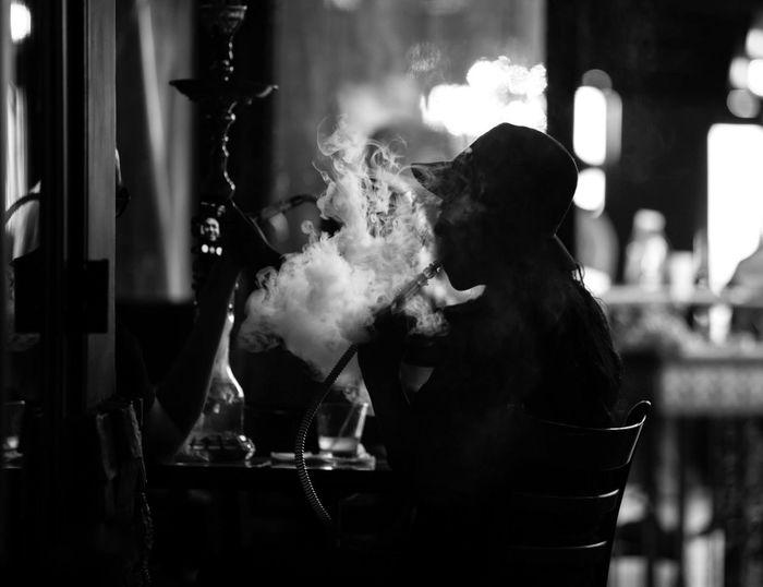 Silhouette woman smoking waterpipe in restaurant