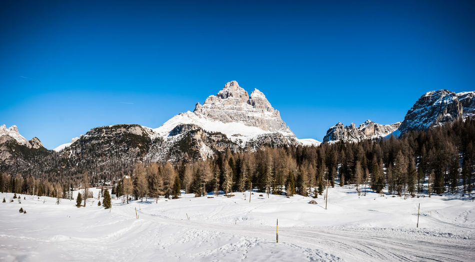 Panoramic view of snow covered mountain against blue sky