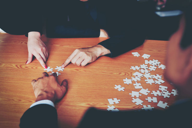 Hand High Angle View Holding Home Interior Human Body Part Human Hand Indoors  Jigsaw Piece Jigsaw Puzzle Leisure Activity Leisure Games Lifestyles Men People Playing Real People Relaxation Table Togetherness Two People