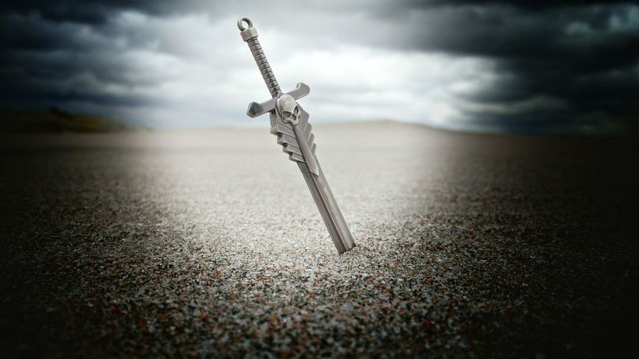 Sword In Sand At Beach Against Cloudy Sky