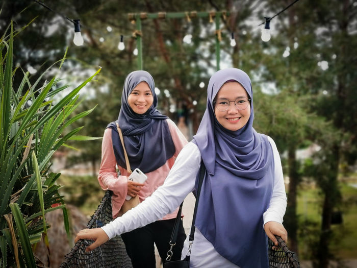 Portrait of smiling friends wearing hijabs standing in forest
