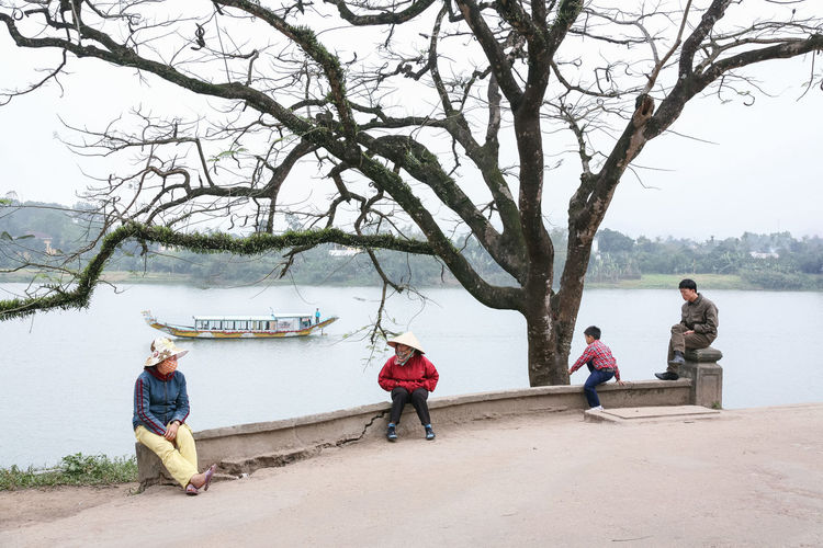 By the Perfume River near Hue, Vietnam Branch Four People National Geographic Outdoors Perfume River  River Riverbank Riverside Sitting South East Asia Street Photography Streetphoto Streetphoto_color Streetphotography Togetherness Tourist Boat Tranquillity Travel Travel Photography Travelling Asia Tree Tree Under The Tree Vietnam Water