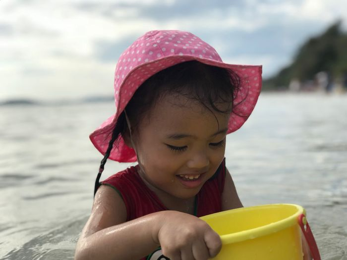 Girl holding bucket while sitting at beach