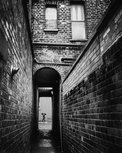 """""""going nowhere"""" Brick Wall Architecture Built Structure Arch Building Exterior Day Real People Outdoors One Person People Raining Day Bnw London London Streets Secret London EyeEm LOST IN London Art Is Everywhere Streetphotography Human Bnw_life Umbrella Street EyeEm LOST IN London Postcode Postcards"""