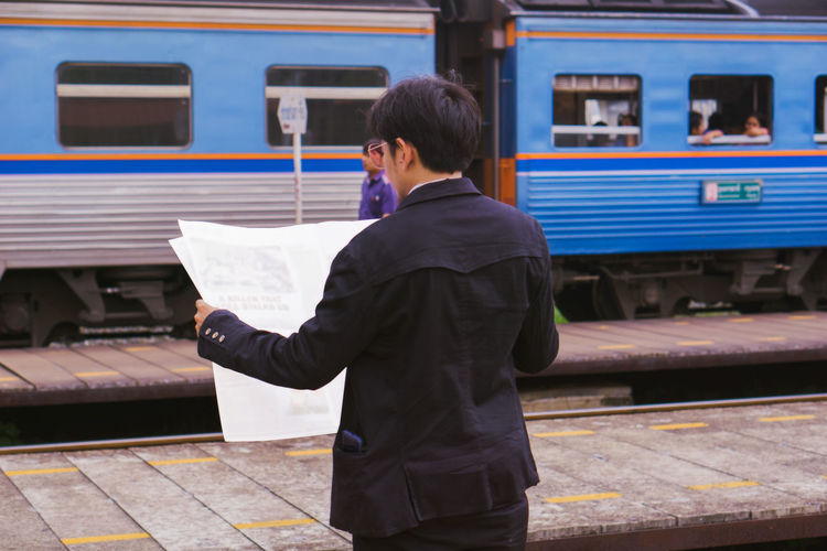 Rear view of man standing at railroad station