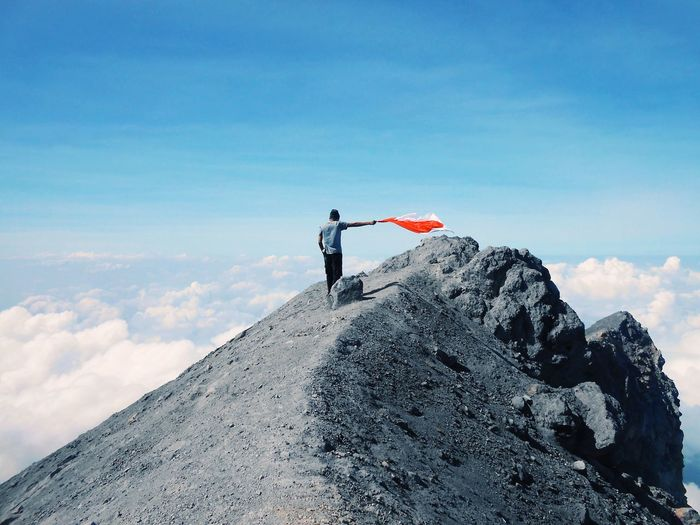 Low angle view of man holding flag while standing rocky mountains sky during sunny day